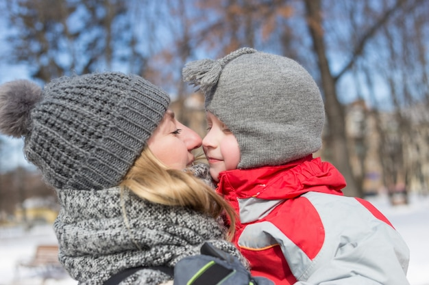 幸せな若い母親と冬の公園で彼女の子供