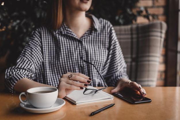 カフェでコーヒーカップとテーブルに座って眼鏡を保持している若い女性を笑顔