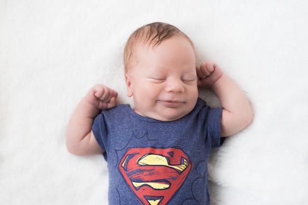 白のスーパーヒーローの衣装で面白い新生児