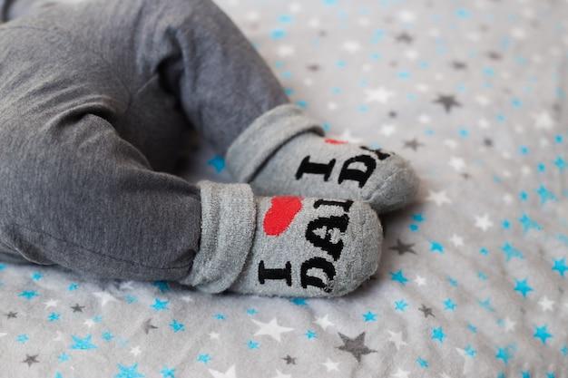 Ноги новорожденного. детские ножки в носках с надписью