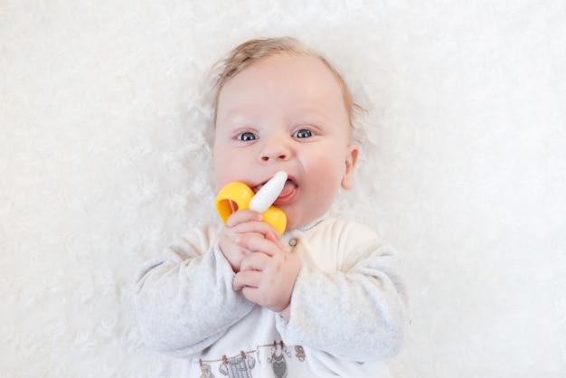 Портрет крупным планом маленький милый мальчик с большими голубыми глазами с игрушкой в руках, грызет банановую игрушку-прорезыватель