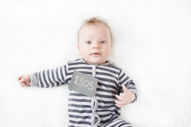 Портрет милого малыша в полосатом костюме с табличкой на груди