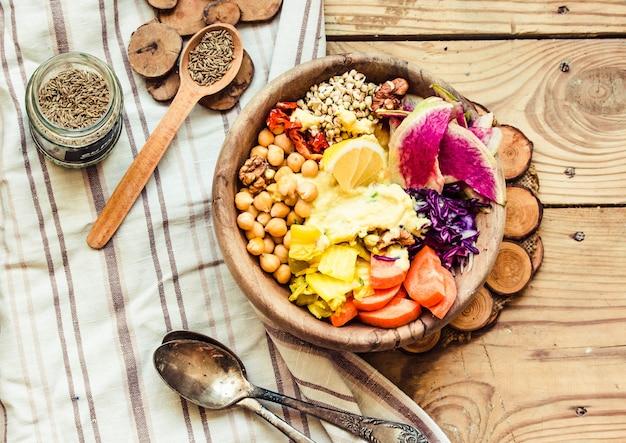 スパイシービーンズ(ひよこ豆)、サンドライトマト、レモン、ナッツ、キムチと木の上のターメリック