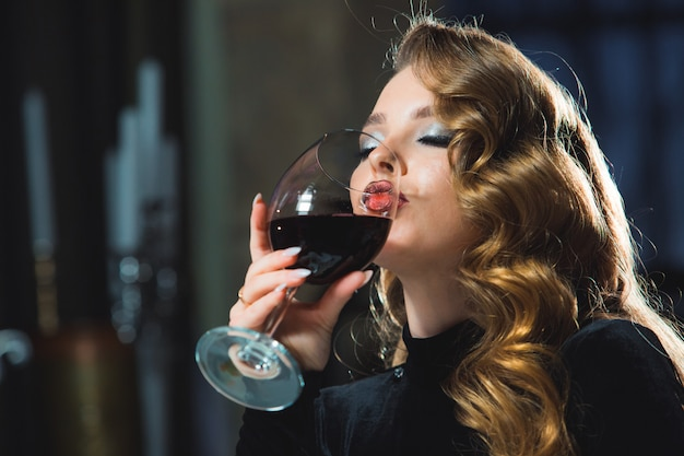Девушка с бокалом красного вина в ресторане