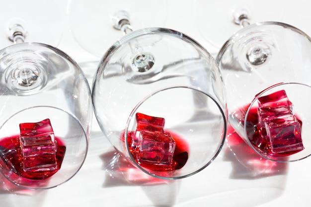 Бокалы красного вина и кубики льда