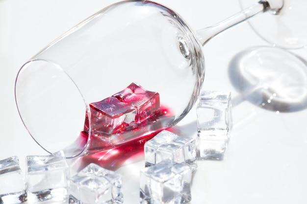 Стакан красного вина и кубики льда