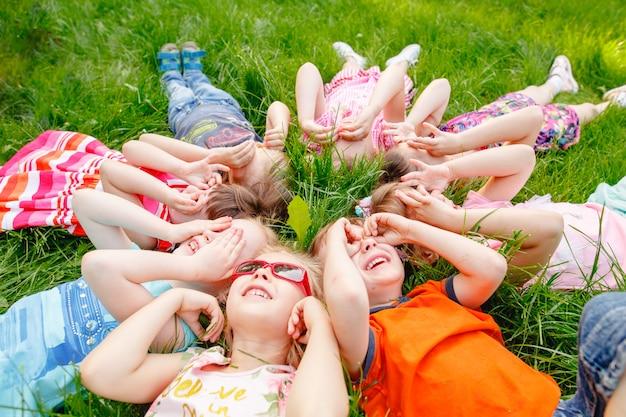 男の子と女の子の幸せな子供たちのグループは、晴れた夏の日に公園の芝生の上を走る
