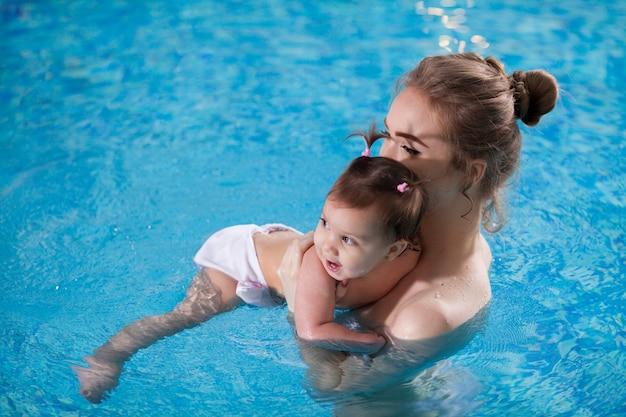 Молодая мама купает ребенка в бассейне.