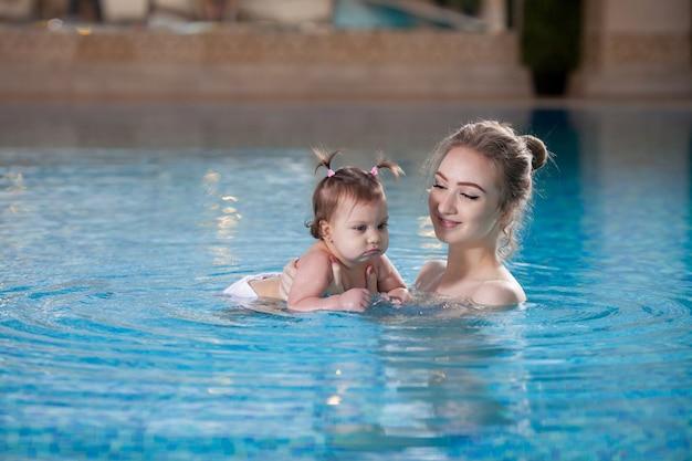 若い母親はプールで赤ちゃんを浸します。