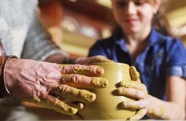 子供を持つ主人は粘土の水差しを作ります。