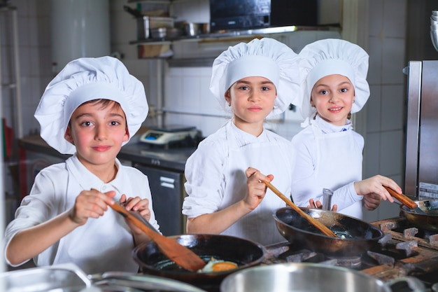 子供たちはレストランのキッチンで昼食を作っています。