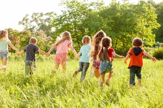 Группа детей, играющих и бегущих в парке на зеленом гозоне.