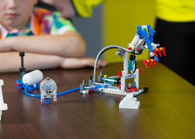Позитивные дети играют и собирают конструктора в детской комнате.