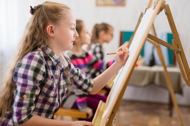 Дети рисуют на мольберте в художественной школе.