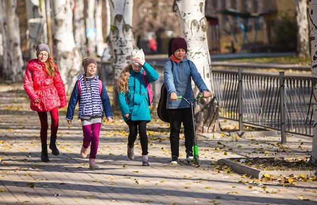 子どもたちは、楽しい会社で歩道で学校に行きます。
