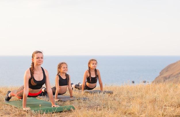 インストラクターは、海の山でヨガの子供たちを訓練します。