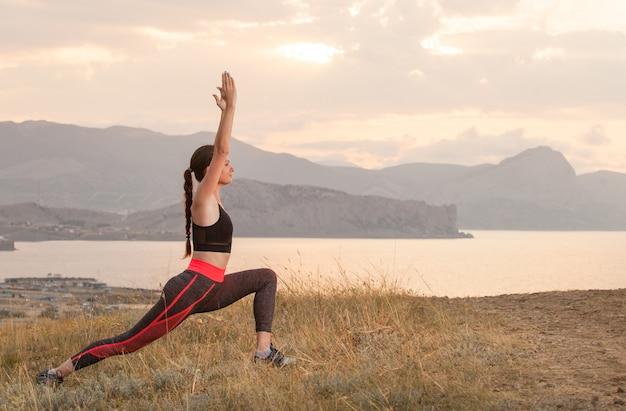 女性は海の山でヨガを練習しています。