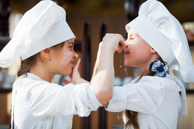二人の女の子が小麦粉の生地を作ります。