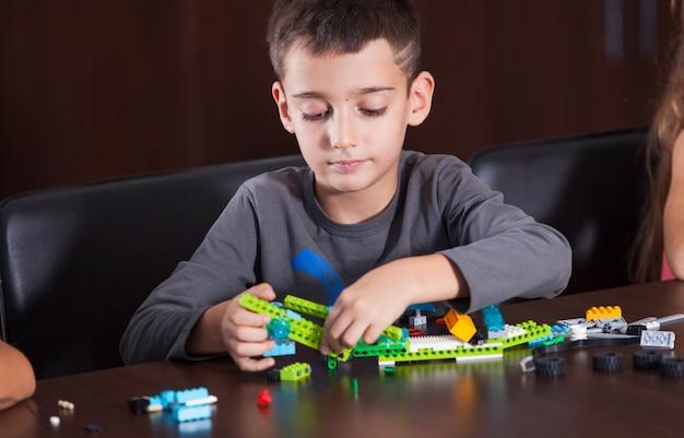 Веселые улыбающиеся дети строят конструктор.