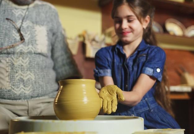 子供を持つ主人は粘土の水差しを成形します。