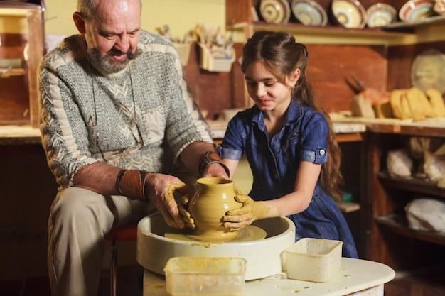 Мастер с ребенком лепит глиняный кувшин.