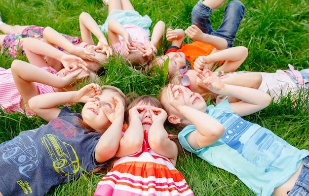 晴れた夏の日、男の子と女の子の幸せな子供たちのグループが公園の芝生で走ります。