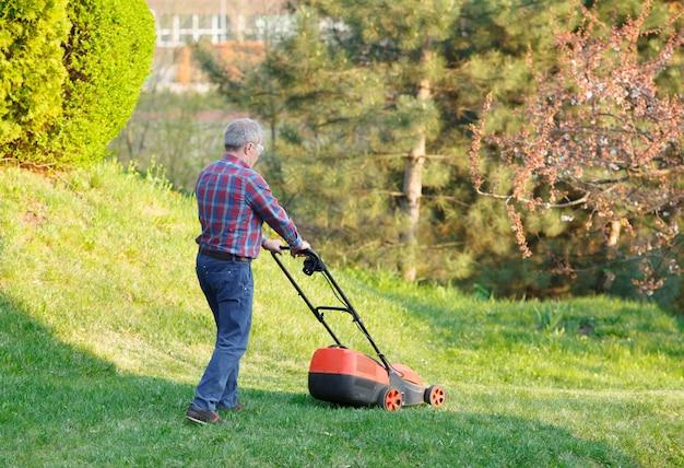 男は芝刈り機で芝生を刈ります。