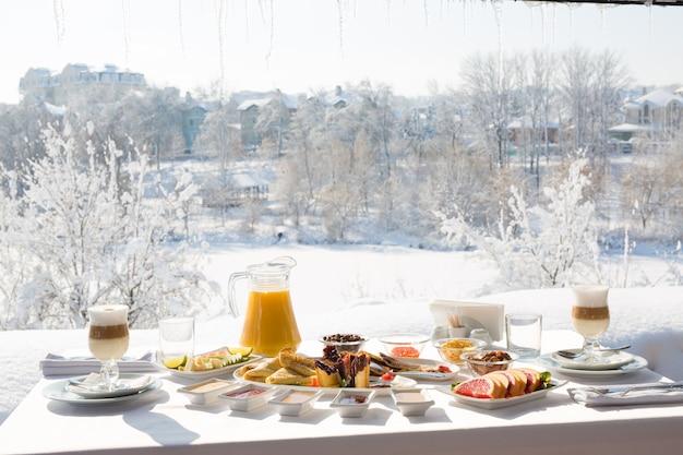 雪の降る冬の屋外でレストランで朝食をとります。