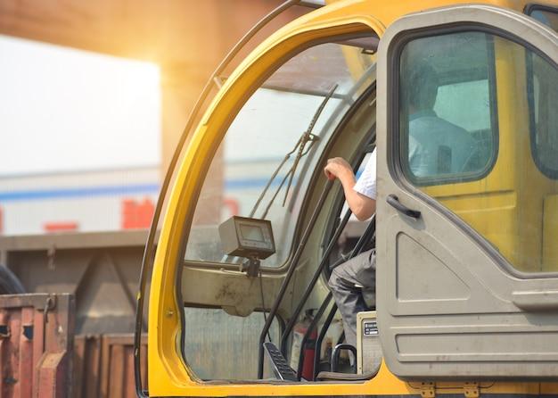 いくつかの機器を持ち上げるためにクレーンを運転する男