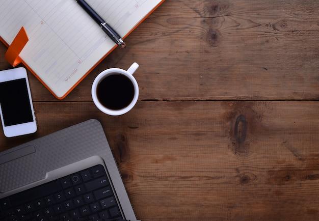 ノートブックスマートフォンのコーヒーやラップトップと職場