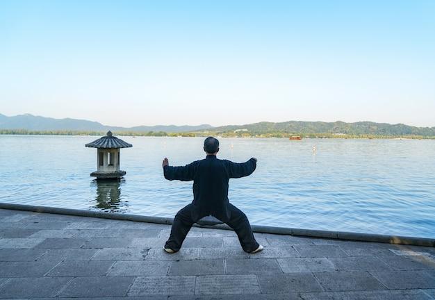 老人は西湖、杭州、中国の側で太極拳を練習しています。