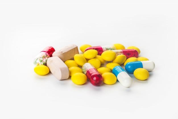 各種カプセルの薬と異なる色の薬の背景
