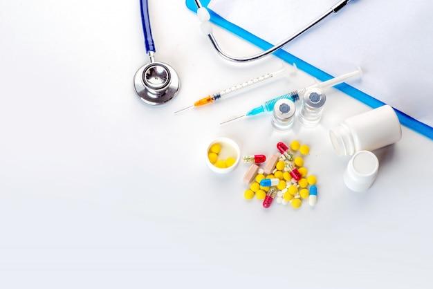 薬瓶注射器温度計と聴診器白い背景の上からこぼれる