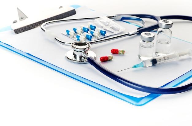 薬瓶注射器温度計と白い背景の上の聴診器からこぼれる丸薬