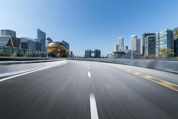 Пустое дорожное покрытие с современными городскими достопримечательностями