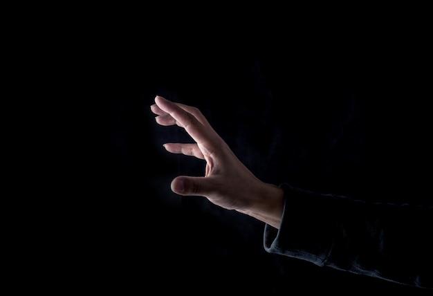 黒い背景にあなたの指を上げる