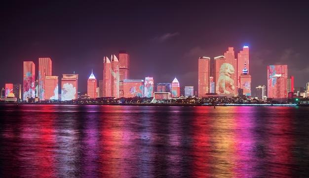 夜、照明ショーは中国の青島の街のスカイラインにあります