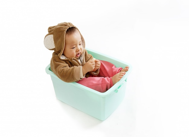 猿の服を着た赤ちゃんが箱に座って食べる