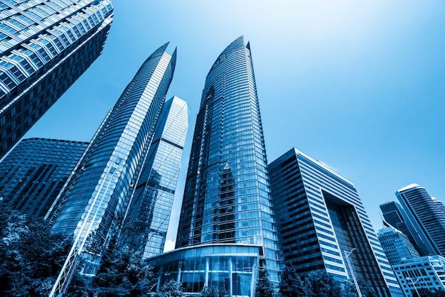 青い近代的なオフィスビルを見上げる