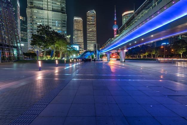 夜、中国上海の歩道橋と高層ビル