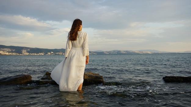 白いロングドレスを着て、ビーチに立っている女性