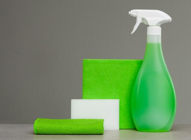 プラスチックディスペンサー、スポンジ、布を使ってほこりを落とすグリーンスプレーボトルの清掃