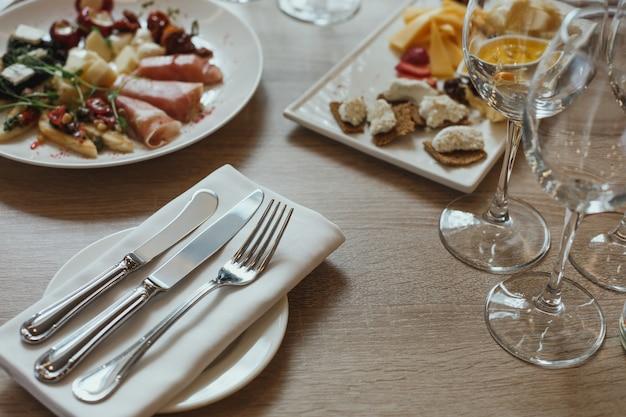 Столовые приборы, закуски и бокалы на деревянном столе в ресторане.