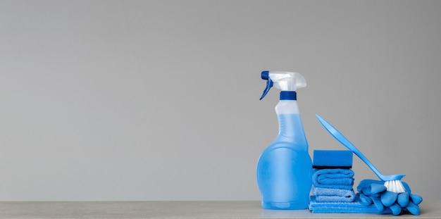 プラスチック製ディスペンサー、スポンジ、食器用のブラシ、ほこり用の布、灰色のゴム手袋で青いスプレーボトルを掃除する