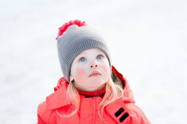 ニット帽とピンクの冬のジャケットの青い目の少女が見上げる。