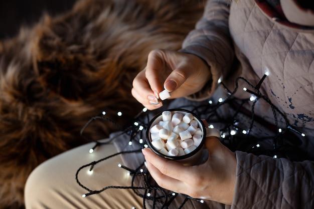 白いエナメルマグカップを保持している彼女の膝の上のクリスマスの花輪を持つ女性