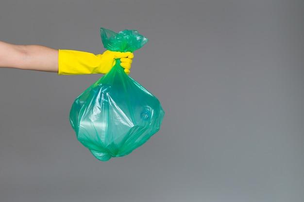 ゴム手袋で女性の手は透明な緑色のゴミ袋を保持します