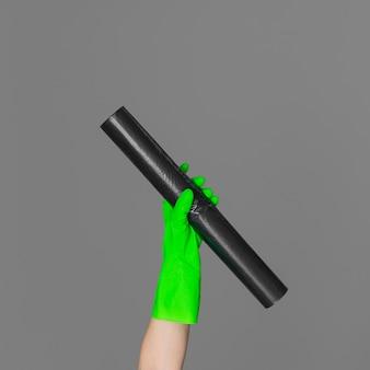 Рука в резиновой перчатке удерживает мешок для мусора