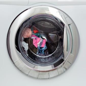 円形の透明なドアハッチ自動洗濯機、およびその中の色のリネンの洗濯。