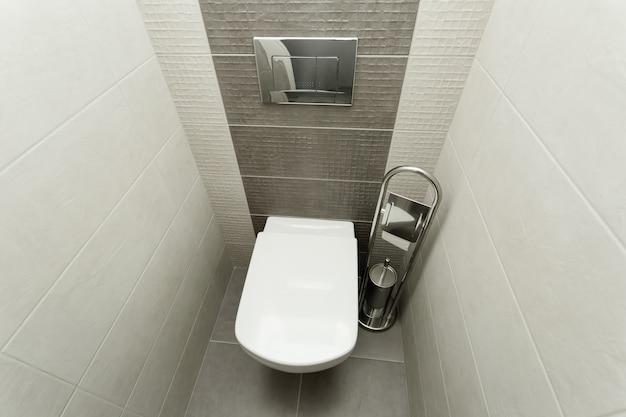 ペーパーホルダーとトイレットブラシ付きのモダンなバスルームの白い便器。